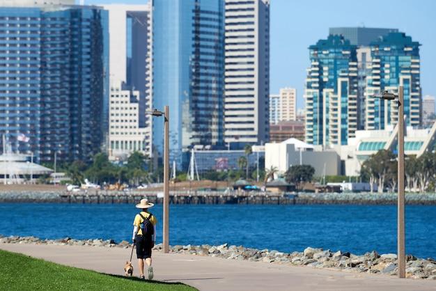 Mujer con sombrero redondo clásico pasear al perro en el parque frente al mar en san diego