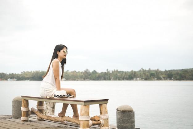 Mujer, con, sombrero, relajante, en, puente