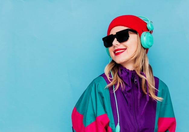 Mujer con sombrero rojo, gafas de sol y traje de los años 90 con auriculares.