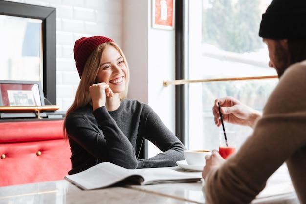 Mujer con sombrero rojo hablando con hombre