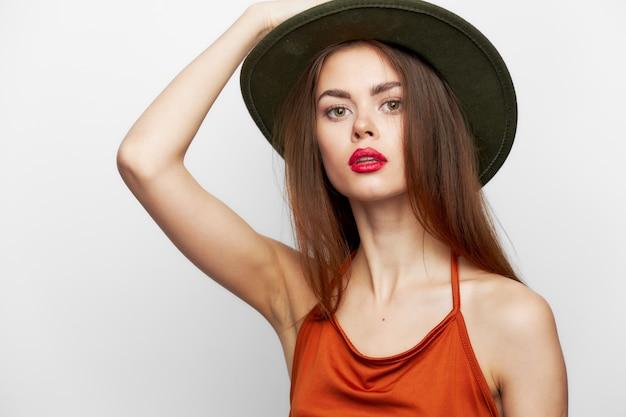 Mujer con sombrero rojo labios mano en cabeza estilo elegante encanto