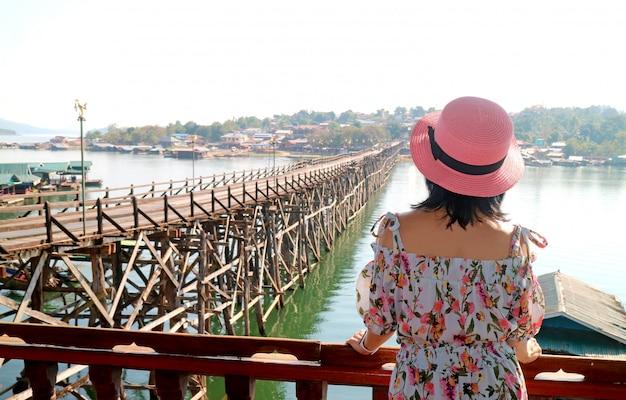 Mujer con sombrero rosa admirando el puente de mon, hito del distrito de sangkhlaburi, tailandia