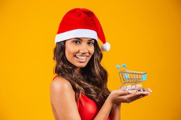 Mujer con sombrero de santa haciendo compras navideñas. ella está mostrando un mini carrito.