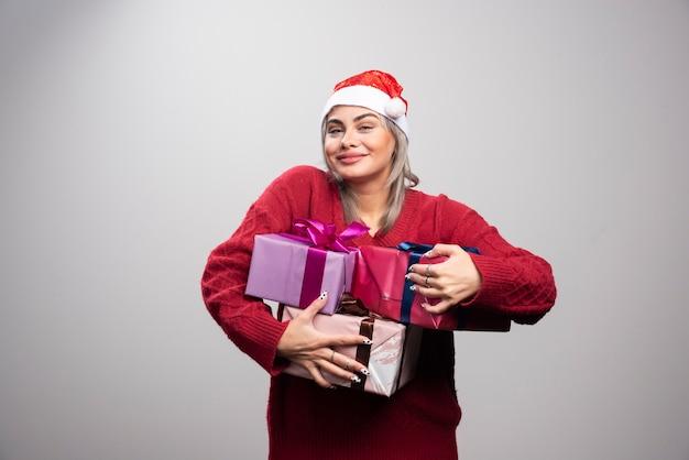 Mujer con sombrero de santa con montón de cajas de regalo.