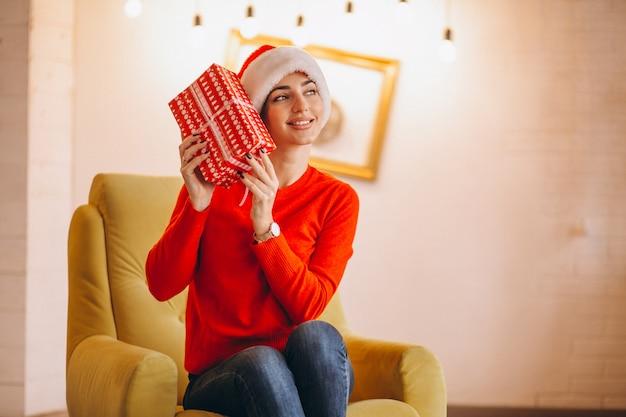 Mujer en el sombrero de santa que se sienta en silla en la navidad con los presentes