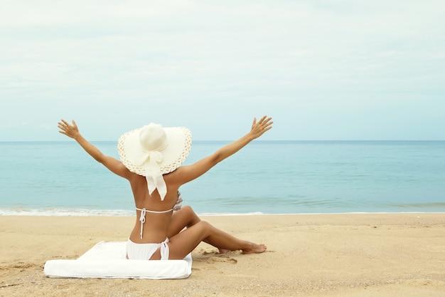 Mujer con sombrero sentada en la playa