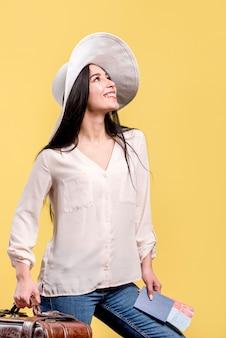 Mujer en sombrero sonriendo y sosteniendo boletos y maleta