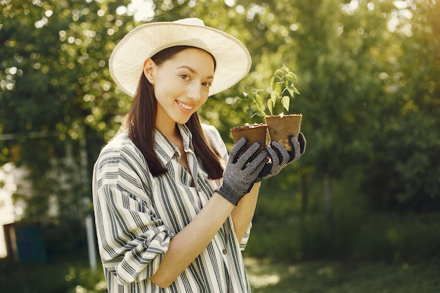 Mujer con sombrero sosteniendo macetas