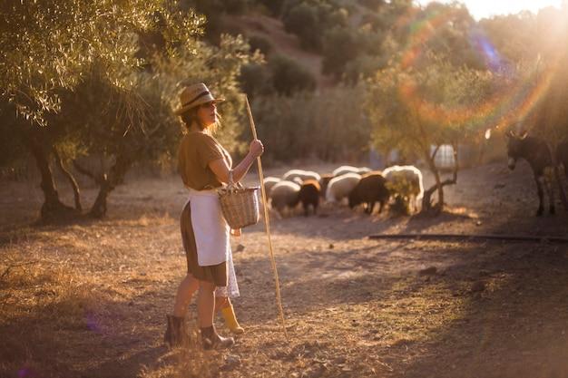 Mujer con sombrero sosteniendo palo pastor de ovejas en la granja