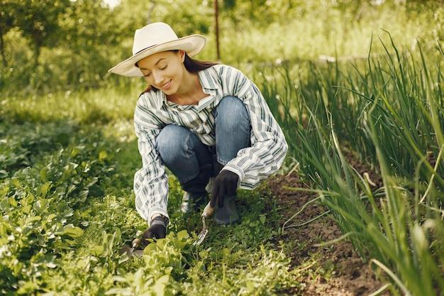 Mujer con sombrero trabajando en un jardín.