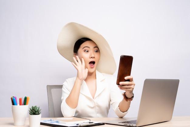 Mujer con sombrero usar teléfono inteligente tomando un selfie en la oficina aislada sobre fondo