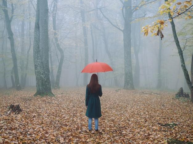 Mujer con sombrilla roja en otoño niebla amarillo deja aire fresco.