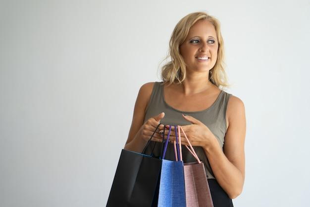 Mujer soñadora feliz con pelo rubio pensando en compra nueva y sosteniendo bolsas de compras.