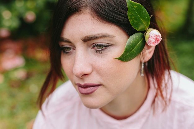Mujer soñadora con flores en cabello castaño