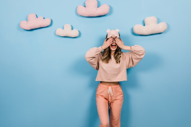 Mujer soñadora en pijama que cubre los ojos en la pared azul