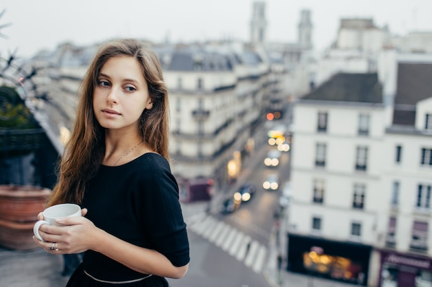 Mujer soñadora con taza en balcón
