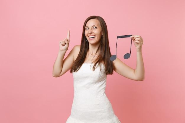 Mujer soñadora en vestido blanco apuntando con el dedo índice hacia arriba mantenga nota musical eligiendo personal, músicos o dj
