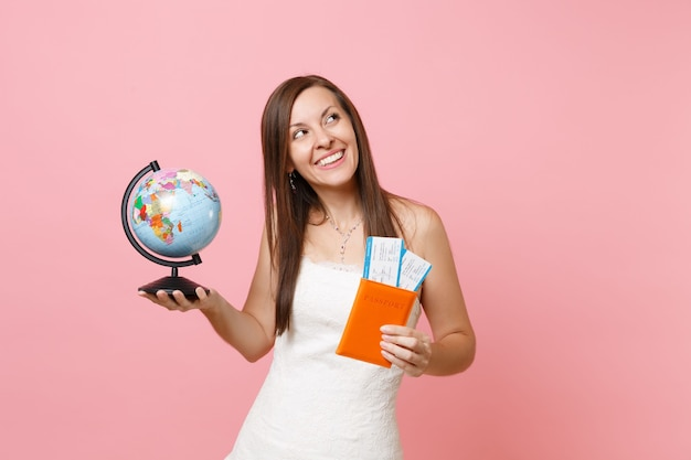 Mujer soñadora en vestido blanco con globo terráqueo, pasaporte boleto de embarque, ir al extranjero, vacaciones