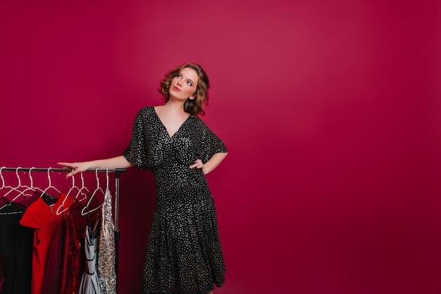 Mujer soñadora en vestido negro retro mirando hacia arriba mientras posa junto a perchas con ropa