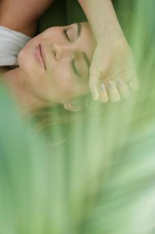 Mujer soñando despierta y planta de la casa borrosa
