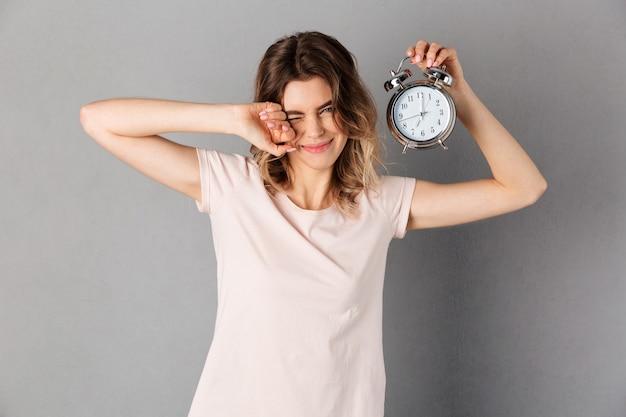 La mujer soñolienta en camiseta despierta mientras sostiene el despertador y sobre gris