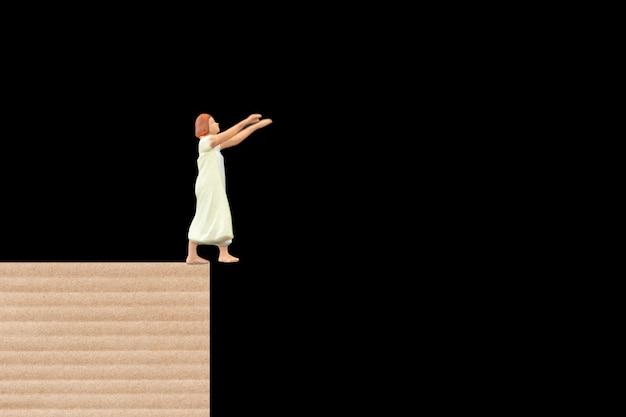 Mujer soñolienta que sufre de sonambulismo en casa sobre fondo negro
