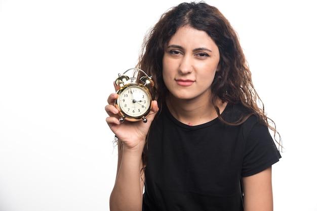 Mujer soñolienta sosteniendo un reloj de alarma sobre fondo blanco. foto de alta calidad