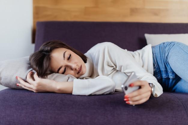La mujer soñolienta sueña en la cama después de un duro día de trabajo