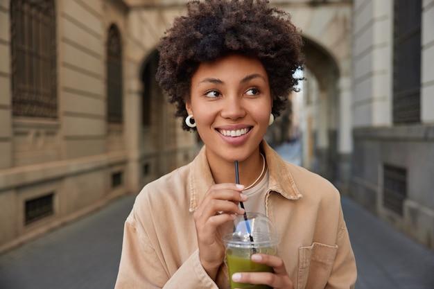 Mujer sonríe ampliamente bebidas refrescantes batidos verdes de paja camina en la ciudad durante el tiempo libre vestida con chaqueta marrón plantea en la ciudad antigua