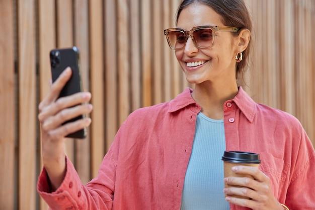 Mujer sonríe ampliamente muestra dientes blancos usa gafas de sol camisa rosa sostiene el teléfono móvil frente a ella hace videollamadas bebe cafeína bebida de vaso de papel