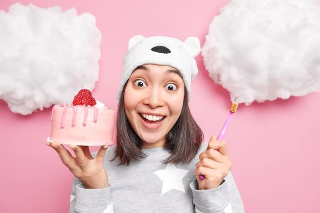 Mujer sonríe con dientes vestida con pijama sostiene un sabroso pastel y un cepillo de dientes tiene caries debido a comer demasiados dulces aislados en rosa