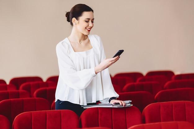 Mujer sonríe y escribe sms en el teléfono