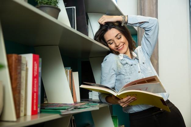 La mujer sonríe mientras lee el libro