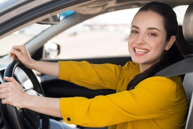 Mujer sonríe y sentada en el auto