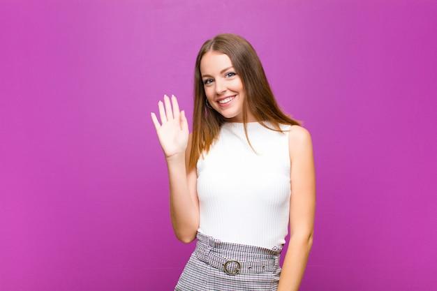Mujer sonriendo alegre y alegremente, saludando con la mano, dándote la bienvenida y saludándote, o diciéndote adiós
