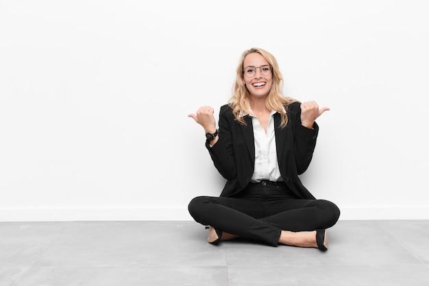 Mujer sonriendo alegremente y luciendo feliz, sintiéndose despreocupada y positiva con ambos pulgares arriba