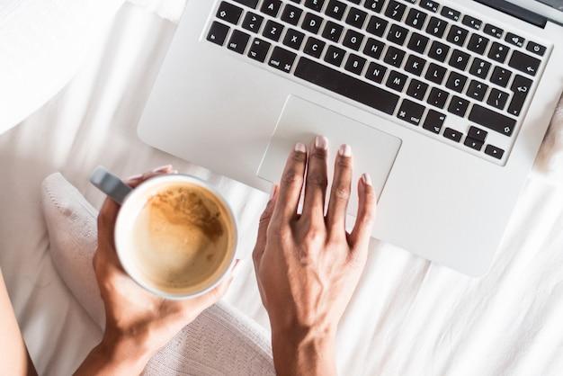 Mujer sonriendo bebiendo un café y trabajando con su computadora en la cama