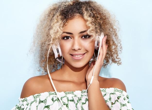 Mujer sonriendo y escuchando música en auriculares