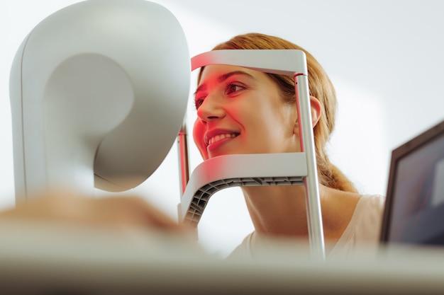 Mujer sonriendo. hermosa joven de ojos oscuros sonriendo mientras tiene un examen de los ojos