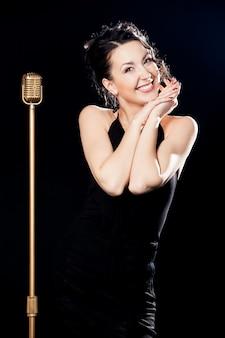 Mujer sonriendo con las manos juntas y un micrófono