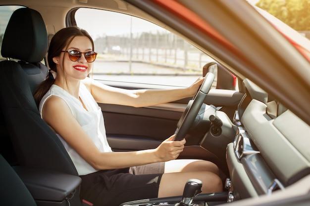 Mujer sonriendo mientras conduce un auto