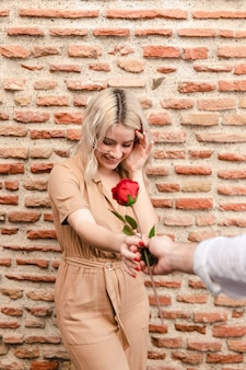 Mujer sonriendo mientras le dan una rosa
