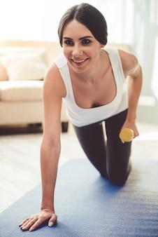 La mujer está sonriendo mientras hace ejercicio con pesas