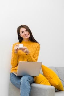 Mujer sonriendo mientras está sentado en el sofá y sosteniendo la taza de café