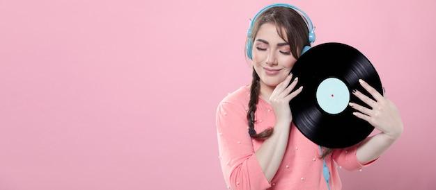 Mujer sonriendo mientras sostiene un disco de vinilo y usa auriculares