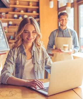 La mujer está sonriendo mientras trabaja con la computadora portátil en el café.
