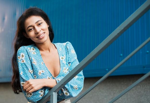 Mujer sonriendo y mirando a la cámara desde las escaleras