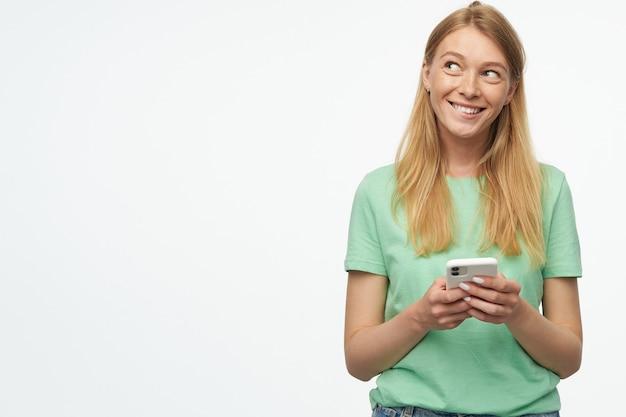 Mujer sonriendo y mirando a un lado en un espacio de copia, sostiene su teléfono celular