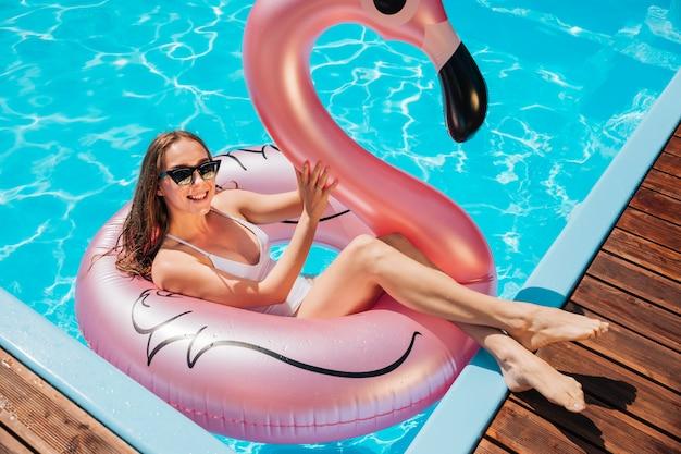 Mujer sonriendo y relajándose en el anillo de natación