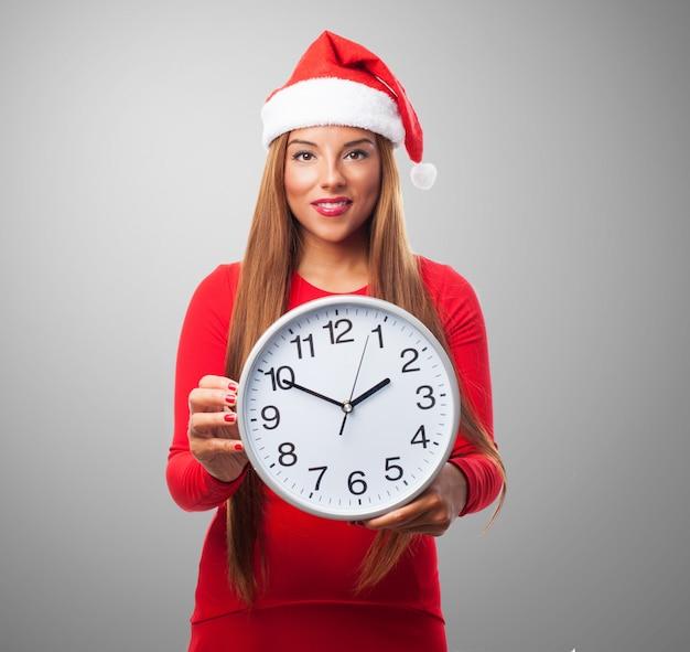 Mujer sonriendo con un reloj grande